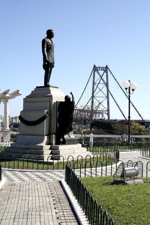 Monumento em Homenagem ao Governador Hercílio Luz tendo ao fundo a Ponte